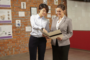 Female asian worker showing caucasian female manager print brochure in gallery of printing and packaの写真素材 [FYI03563149]