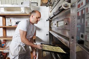 Baker working in bakeryの写真素材 [FYI03563244]
