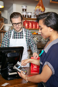 Customer in bakery paying for goods, using card machine, mid sectionの写真素材 [FYI03563282]