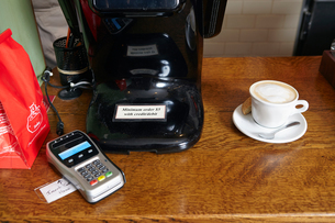 Coffee on counter in bakery, beside card payment machineの写真素材 [FYI03563285]