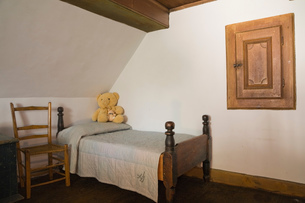 Old wooden chair and single bed in a bedroom in old (1785) fieldstone cottage style residential homeの写真素材 [FYI03563323]