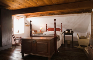 Double bed and old wooden storage chest in the master bedroom in old (1785) fieldstone cottage styleの写真素材 [FYI03563324]