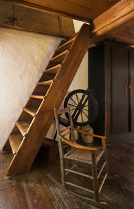 Old wooden rocking chair and spinning wheel next to stairs in the master bedroom leading to attic inの写真素材 [FYI03563325]