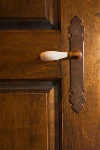 Close-up of a white porcelain door handle on old wooden door of master bedroom in cottage style logの写真素材 [FYI03563334]