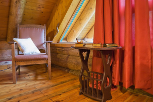 Brown wooden leather chair and side table in master bedroom in Scandinavian cottage-style log home,の写真素材 [FYI03563344]