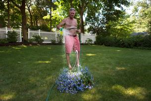 Senior man in garden watering flower hanging basketの写真素材 [FYI03563350]