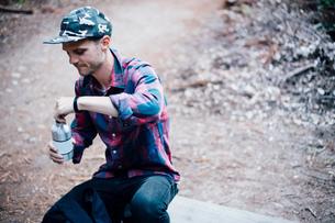 Man opening bottled water, Big Sur, California, USAの写真素材 [FYI03563361]