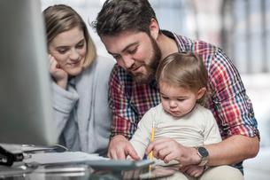 Couple sitting at desk, toddler sitting on man's lap watching man drawの写真素材 [FYI03563396]