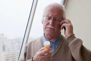 Senior man reading label on pill bottle at homeの写真素材 [FYI03563485]