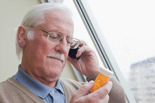 Senior man reading label on pill bottle at homeの写真素材 [FYI03563487]