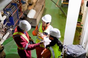 Engineers in brainstorming session on oil rigの写真素材 [FYI03563533]