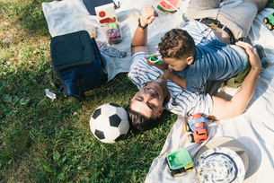 Overhead view of young man playing with toddler son on picnic blanket in Pelham Bay Park, Bronx, Newの写真素材 [FYI03563591]