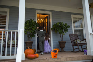 Brother and sister trick or treating at neighbour's front doorの写真素材 [FYI03563647]
