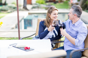 Romantic mature couple making a red wine toast at garden tableの写真素材 [FYI03563708]