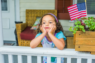Bored girl waiting on porch on Independence Dayの写真素材 [FYI03563745]