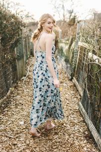 Young woman walking along rural farm pathway, rear viewの写真素材 [FYI03563783]
