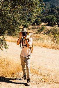 Man looking at camera, photographing, Malibu Canyon, California, USAの写真素材 [FYI03563830]