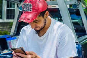 Man wearing baseball cap using smartphoneの写真素材 [FYI03563845]