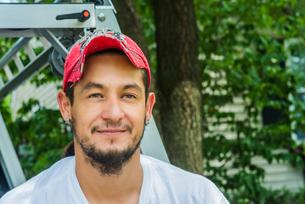 Portrait of man wearing baseball cap looking at camera smilingの写真素材 [FYI03563846]