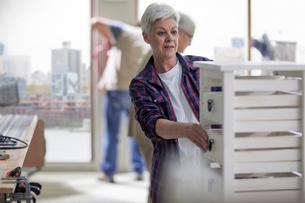 Senior female carpenter checking drawers in furniture making workshopの写真素材 [FYI03563893]