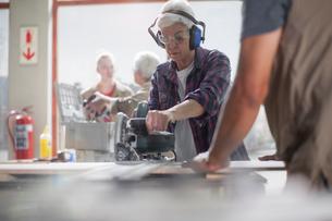 Senior female carpenter using power saw in furniture making workshopの写真素材 [FYI03563909]