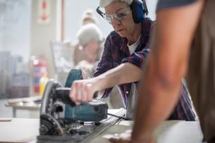 Senior female carpenter using power saw in furniture making workshopの写真素材 [FYI03563914]