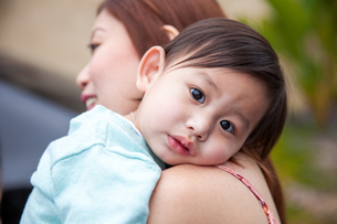 Portrait of brown eyed baby boy with head on his mothers shoulderの写真素材 [FYI03563942]