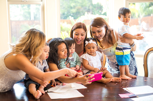 Woman taking selfie with mothers and babies at dining tableの写真素材 [FYI03563952]