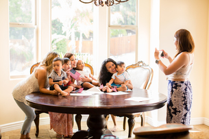 Woman taking photograph of mothers and babies at dining tableの写真素材 [FYI03563953]