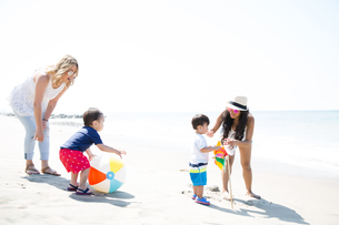 Two mothers and baby sons playing with beach ball and pinwheel on beach, Malibu, California, USAの写真素材 [FYI03563959]