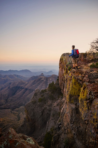 Backpacker looking out from ridge at dusk, Big Bend National Park, Texas, USAの写真素材 [FYI03563987]