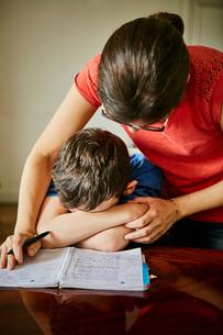 Mother comforting upset son doing homeworkの写真素材 [FYI03564072]