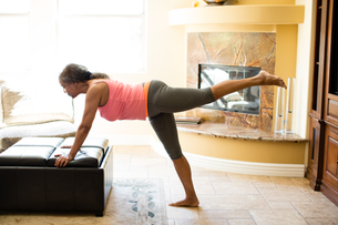 Side view of woman leaning against pouffe doing stretching exerciseの写真素材 [FYI03564099]