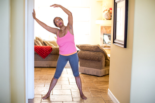 Woman with arms raised doing stretching exerciseの写真素材 [FYI03564101]