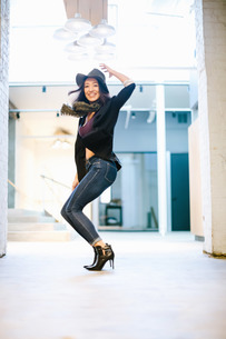 Young woman posing, knees bent, in front of buildingの写真素材 [FYI03564174]