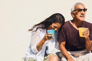 Senior couple sitting on beach, laughing, holding cold drinks, Long Beach, California, USAの写真素材 [FYI03564197]