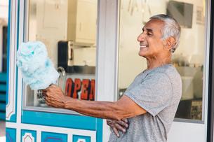 Senior man holding cotton candy, Long Beach, California, USAの写真素材 [FYI03564206]