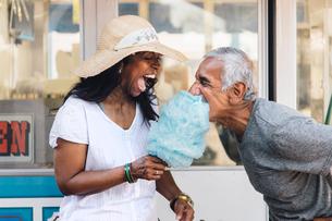 Senior couple eating cotton candy, laughing, Long Beach, California, USAの写真素材 [FYI03564208]