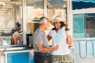 Senior couple standing beside refreshment stand, holding cotton candy, Long Beach, California, USAの写真素材 [FYI03564209]