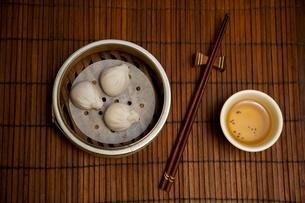 Asian dumplings, tea and chopsticks on bamboo matの写真素材 [FYI03564214]