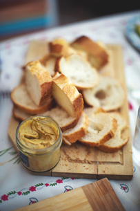 Sliced bread on chopping board with open jar of mustardの写真素材 [FYI03564241]