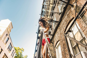 Woman climbing fire escape ladder of apartment building, Boston, MA, USAの写真素材 [FYI03564318]