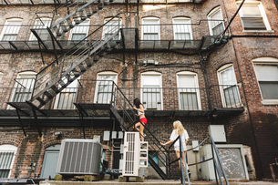 Women climbing fire escape ladder of apartment building, Boston, MA, USAの写真素材 [FYI03564320]
