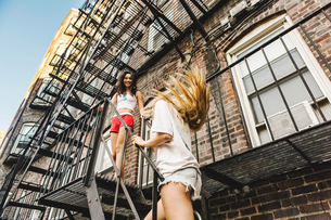 Women climbing fire escape ladder of apartment building, Boston, MA, USAの写真素材 [FYI03564321]