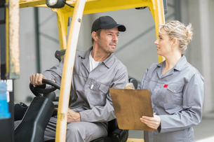 Factory supervisors with clipboard talking to forklift driver at packaging factoryの写真素材 [FYI03564400]