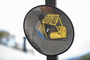 Convex mirror image of forklift driver at packaging factoryの写真素材 [FYI03564402]