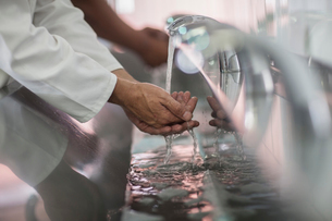 Close up of two factory workers washing hands in packaging factoryの写真素材 [FYI03564414]