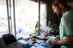 Man preparing order in fast food trailerの写真素材 [FYI03564437]