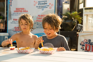 Two young boys eating fast food beside fast food trailerの写真素材 [FYI03564448]