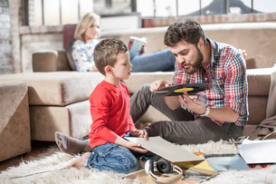 Father showing vinyl record to son at homeの写真素材 [FYI03564522]
